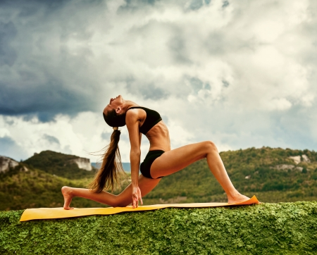 warrior pose: Slim young woman makes warrior yoga pose  Stock Photo