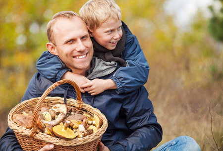 Father and son are happy that they have found a basket full of mushrooms photo