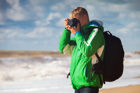 Outdoor photography  Young man with camera makes sea snapshot photo