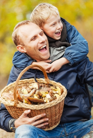 Father with son happy smiling that they have a basket full of mushrooms photo