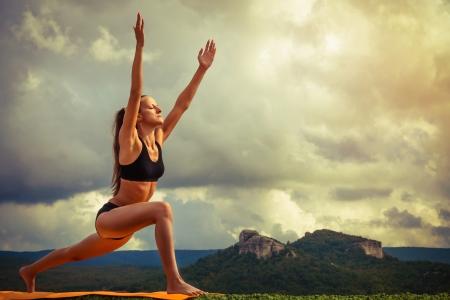makes: Young woman makes sun salutation yoga pose Stock Photo