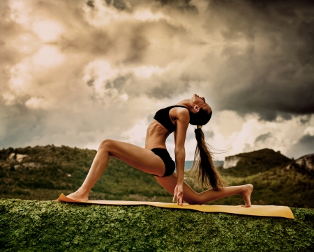 Slim young woman makes warrior yoga pose  Stock fotó