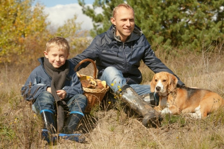 Father with son and pet resting on the forest glade after mushroom picking photo