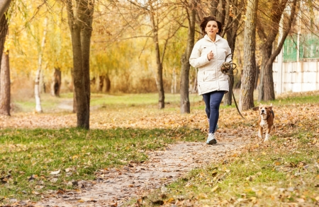 Young woman jogging with her pet in autumn park photo