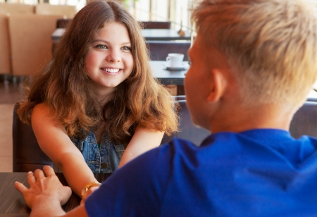 Closeup portrait beautiful smiling young girl sitting in cafe with boyfriend photo