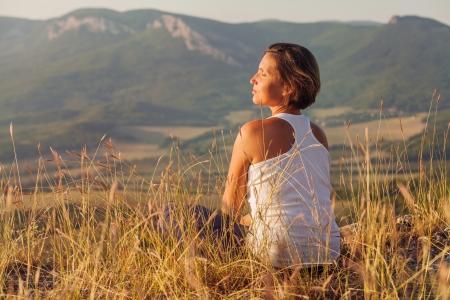 gently: Sitting in meditation pose woman enjoyed with gently shining sunrise