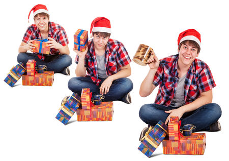 Cheerful young man dressed in santa hat found gift in box photo