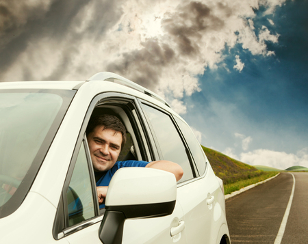 lonely road: Man driving his new car on the lonely road Stock Photo