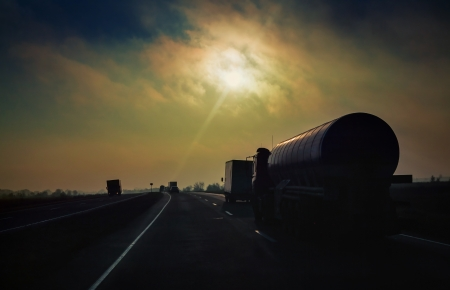 sihlouette: Gasoline tanker rides the highway in the evening sun rays