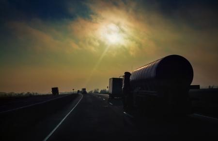 cami�n cisterna: Petrolero de la gasolina monta la carretera en los rayos del sol de la tarde