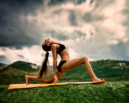 Slim young woman makes warrior yoga pose  photo