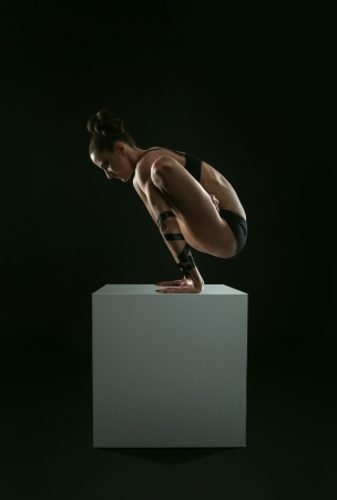 Girl make pendulum yoga pose balancing on straight hands on the white cube photo