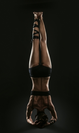 woman black background: Athletic young woman makes headstand yoga pose