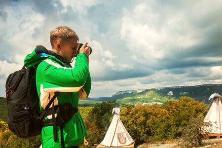 hombre disparando: Hombre joven que hace disparos al aire libre en plato de montaña Foto de archivo