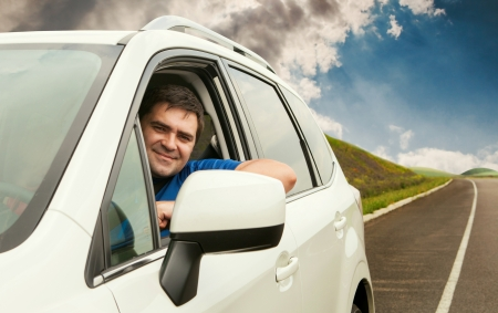 Happy owner driving his new car on the lonely road