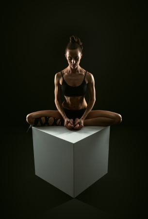 Slim athletic woman doing stretching yoga exercise sitting om white cube photo