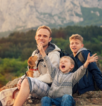 Happy family on mountain walk  Father with sons and pet Standard-Bild