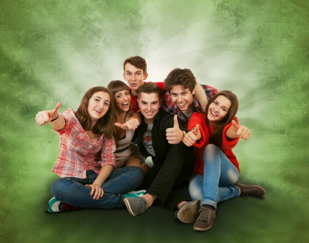 Happy smiling teenagers group on bright green  Stock Photo