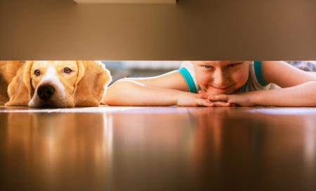 Küçük bir şaka ortakları - köpek arkadaşı ile çocuk yatağın altında görünüyor Stok Fotoğraf
