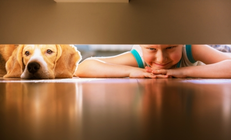 Little prank partners - boy with doggy friend looks under the bed photo