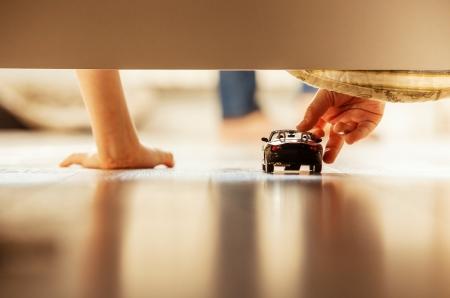 Jongen spelen met speelgoed auto overhang van het bed