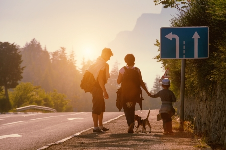Family backpackers goes on mountain road at sunset Standard-Bild