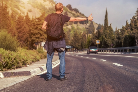 hitch hiker: Hitchhiking traveler try to stop car on the mountain road Stock Photo