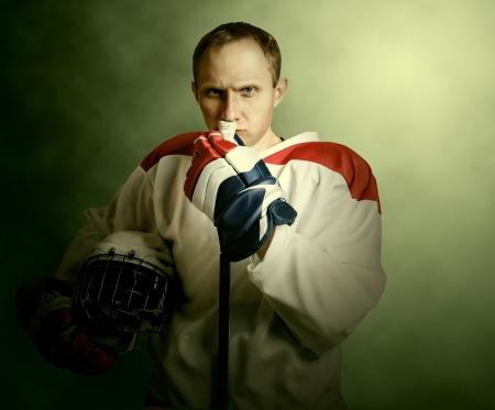 The portrait Ice hockey player on dramatick background  photo