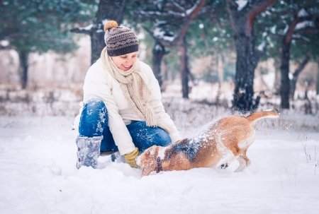 Happy woman playing with her dog in snow in winter park