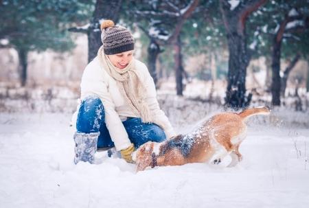 mujer con perro: Mujer feliz que juega con su perro en la nieve en el parque de invierno