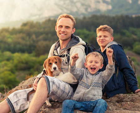 dog rock: Active leisure - father with sons on mountain walk Stock Photo