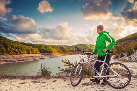 stopped: Young man cyclist stopped for enjoy with beautiful mountain lake view Stock Photo