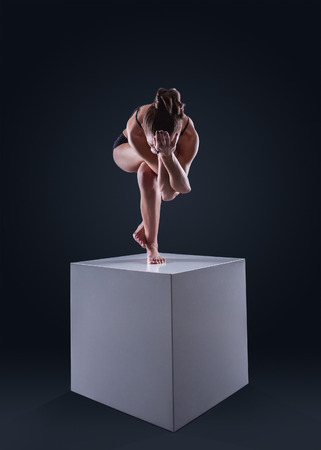 Slim woman makes yoga eagle pose on white cube photo