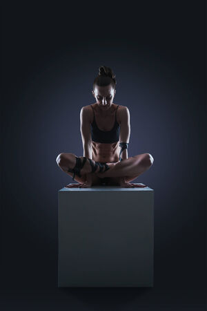 Slim woman sitting on white cube in cocke yoga pose photo