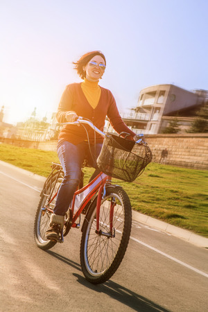 Happy young woman ride by bicycle photo