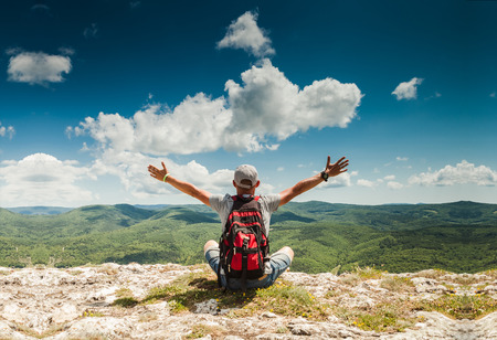 Man greeting amazing rich nature on the top of mountain Standard-Bild