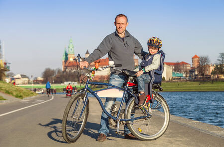 Father with little son walk togeter on bike in city photo