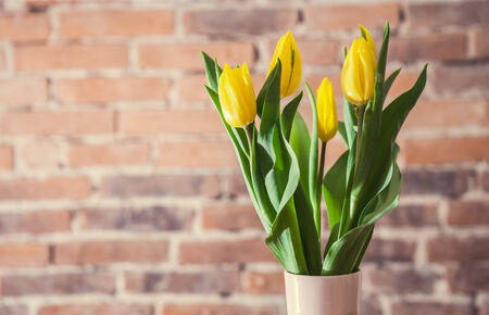 Brick wall background with yellow tulips bouquet photo
