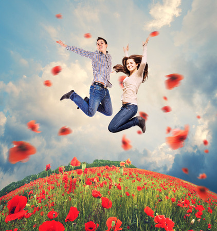 Happy young couple jumping into the sky over poppies field photo