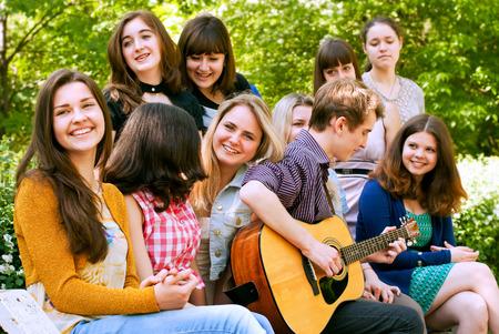 Teen boy singin by guitar for girls photo