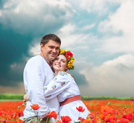 Happy couple in national ukrainian dress on poppies field photo
