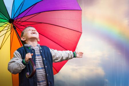 lluvia paraguas: Retrato de niño feliz con el paraguas del arco iris brillante Foto de archivo