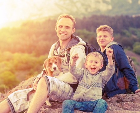 Active leisure - father with sons on mountain walk photo