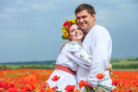Happy ukrainian couple in blossom poppies field photo