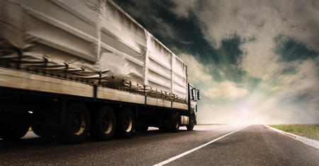 Big tented truck on the lonely highway Stock Photo