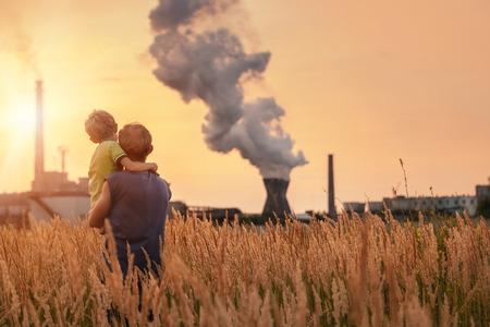 Ecologische concept beeld Vader met zoon kijken op chemische fabriek uitstoot bij zonsondergang tijd