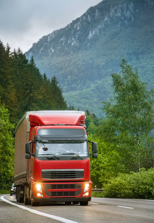 Red truck on mountain highway in the evening Standard-Bild