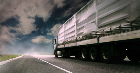 wheel: Big tented truck on the lonely highway Stock Photo