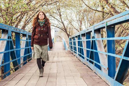 bata blanca: Chica joven caminando sobre el puente a principios de primavera