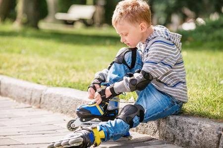 niño en patines: El niño pequeño ata su patín de ruedas sentado en la acera